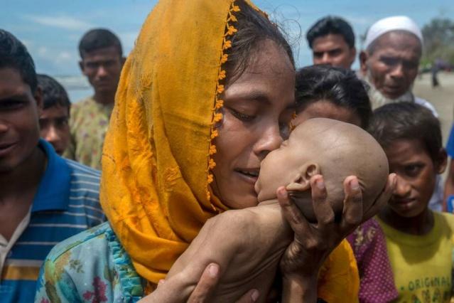 """Hanida Begüm Shah Porir Dwip sahili yakınında teknelerinin alabora olması sonucu boğulan oğlu Abdul Mesud'u öperken, Bangladeş, 14 Eylül.  """"Afganistan kamplarında ülke içinde yerlerinden edilmiş insanlar gördüm. Kendi memleketim Keşmir'de neredeyse her gün ölüme ve yıkıma şahit oldum. Ama 13 Eylül'de geldiğim ve sadece birkaç saat için Cox's Bazar'da, Bangladeş'te bulunduğum yer için söyleyebilirim ki bu farklı bir şeydi. Söylediğim şey bu krizin sadece şeffaf bir ölçüsü. Burada bakacağınız her yerde yemek için, su için, sığınak için veya Myanmar'dan bir tanıdık görmek için çaresiz bir arayış vardı.  Fotoğrafladığım insanlarla konuşmak gibi bir alışkanlığım var. Yerel halka iletişime geçmeme yardım eden kişi Cox Bazar'lıydı ve onun söylediğine göre Rohingya dili ve kendisinin yerel dili birbiriyle benziyormuş. Mülteciler konuşmaya istekli, ancak çoğu zaman neyin içinde olduklarını açıklayamayacak kadar yorgun ve bitkin durumdaydılar.""""  """"Bir Fotoğrafçının Arakan Sürgününden Çektiği Trajik Kareler"""" başlıklı çalışma Mepa News tarafından Türkçeleştirildi. Çalışmanın fotoğraf ve metinleri Dar Yasin tarafından oluşturulurken, çalışmayı Andrew Katz yayına hazırladı."""