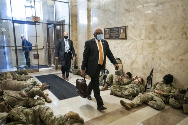 ABD Başkanı Donald Trump'a yönelik azil süreci devam ederken, ABD Ulusal Muhafızları 6 Ocak'ta baskına uğrayan başkent Washington'daki kongre binasında nöbet tutmaya devam ediyor. ABD Temsilciler Meclisi Üyesi, James Clyburn (ortada) kongre binasına girerken uyuyan ulusal muhafızların arasından geçti.