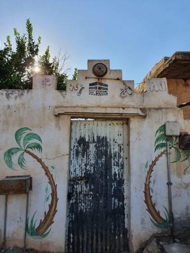 Arap dünyasında (özellikle Suriye ve Filistin bölgesinde) yaygın bir âdet vardır: Hacca giden insanların evlerinin dış cephesi ve kapısı, komşuları tarafından Kâbe motifleriyle ve yazılarla süslenir.   Fotoğraf, İdlib'den...   Kamera M. Salih Topbaş Kaynak: mecra
